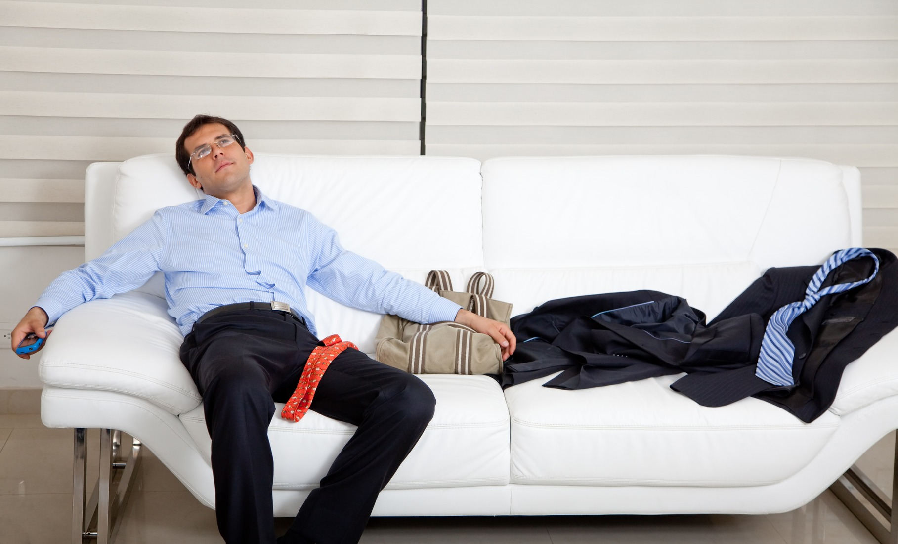 Exhausted business man lying on the sofa with a mess