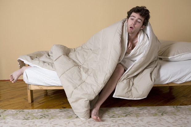 Young man wrapped in blanket on edge of bed