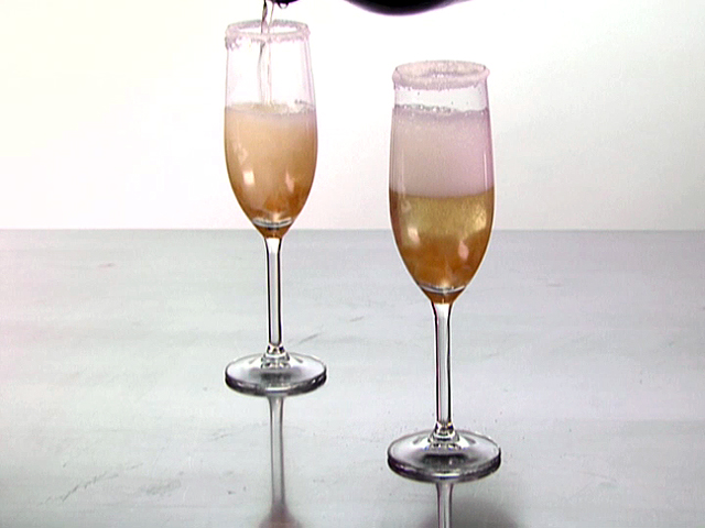 A unique and different drink is being poured into two glasses. These glasses hold a champagne cocktail that is good for you and contains an infusion of ginger and candied ginger.
