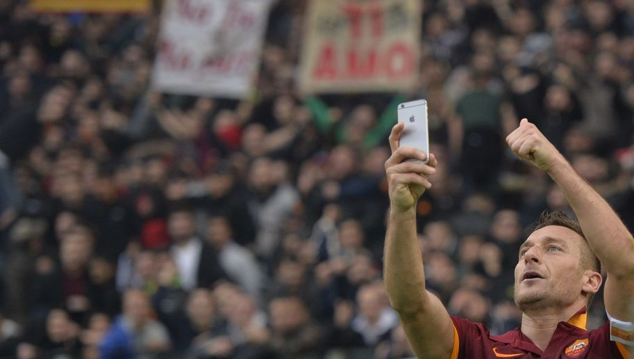 "Roma's forward Francesco Totti celebrates by taking a ""selfie"" with fans after scoring a second goal during the Italian Serie A football match on January 11, 2015 at Rome's Olympic stadium. AFP PHOTO / ANDREAS SOLARO (Photo credit should read ANDREAS SOLARO/AFP/Getty Images)"