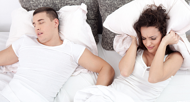 Young couple in bed woman trying to sleep while a man is snoring