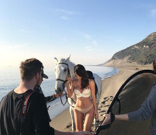"""Aurela Hoxha shfaqet me bikini pranë një kali të bardhë në bregdet. Xhirime të realizuara tek """"Rëra e hedhur""""."""