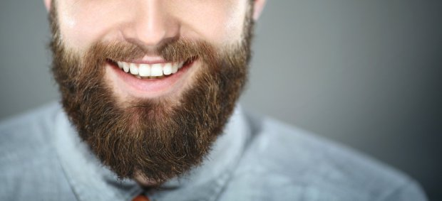 Closeup portrait of smiling unrecognizable bearde man. He's facing the camera and smiling with perfect set of teeth. Wearing light blue smart casual shirt. Shot oer gray background.