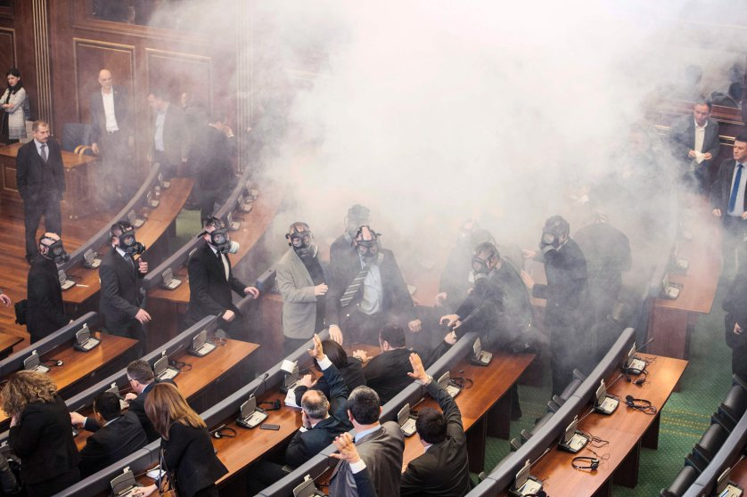 Kosovo police officers wearing gas masks inspect the parliament, after tear gas was launched by opposition lawmakers, disrupting the first parliamentary session of the year in Pristina on Feb. 19, 2016. Angry over a government deal with Serbia and demanding snap elections, the united opposition has effectively blocked parliamentary proceedings since October with their tear gas protests.