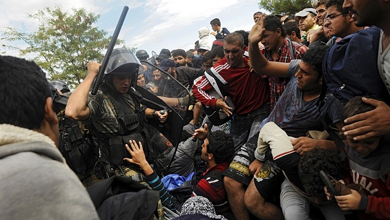 A Macedonian police officer raises his baton towards migrants to stop them from entering into Macedonia at Greece's border,near the village of Idomeni, Greece, August 22, 2015. Thousands of rain-soaked migrants stormed across Macedonia's border on Saturday as police lobbed stun grenades and beat them with batons, struggling to enforce a decree to stem their flow through the Balkans to western Europe. Security forces managed to contain hundreds in no-man's land. But several thousand others – many of them Syrian refugees - tore through muddy fields to Macedonian territory after days spent in the open without access to shelter, food or water. REUTERS/Alexandros Avramidis      TPX IMAGES OF THE DAY