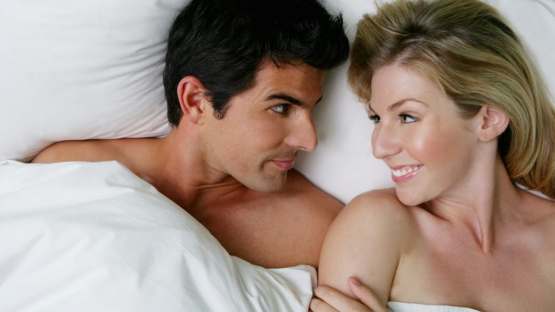 Young happy couple relaxing in bed.