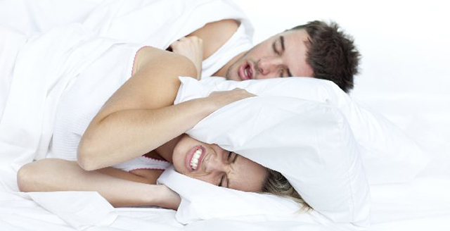 Couple in bed while the woman is trying to sleep