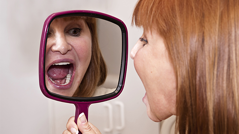 woman at the dental officelooking at her new dental implants. Bright dental light on patients mouth to show her the proper color of he new teeth.