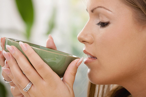 Closeup portrait of beautiful girl drinking tea, side view.