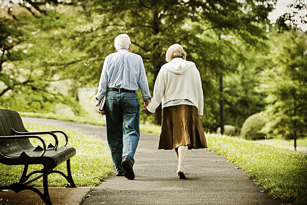 Senior couple walking in park.