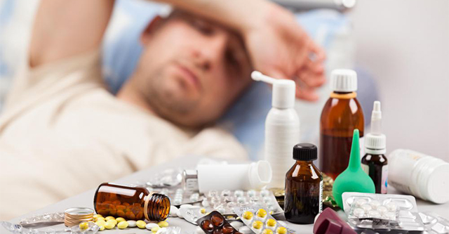 man-with-hand-over-his-head-feeling-ill-in-background-with-close-view-of-pills-and-medicine