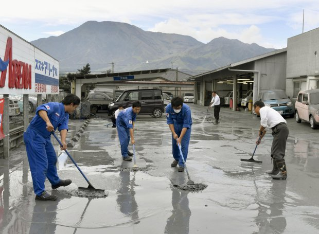 Auto dealership workers clean volcanic ash from the eruption of Mount Aso, back, in Aso city, Kumamoto prefecture, on the southern Japanese main island of Kyushu, Saturday, Oct. 8, 2016. Mount Aso has sent huge plumes of gray smoke as high as 11 kilometers (6.8 miles) into the air in one of the volcano's biggest explosions in years. The Japan Meteorological Agency says early Saturday's explosion also blew off bits of volcanic rock and ash, and raised the alert level for the area, extending the entry ban from just around the volcanic mouth to the mountain itself. (Hiroko Harima/Kyodo News via AP)