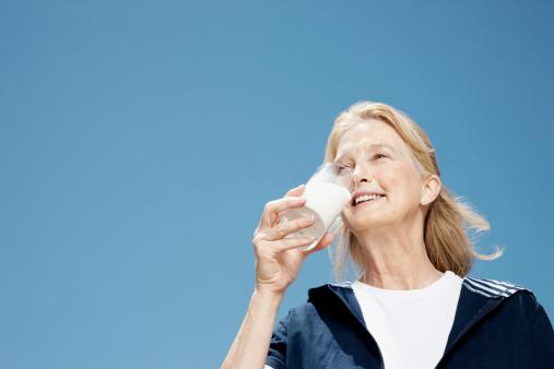 Smiling elderly woman drinking glass of milk