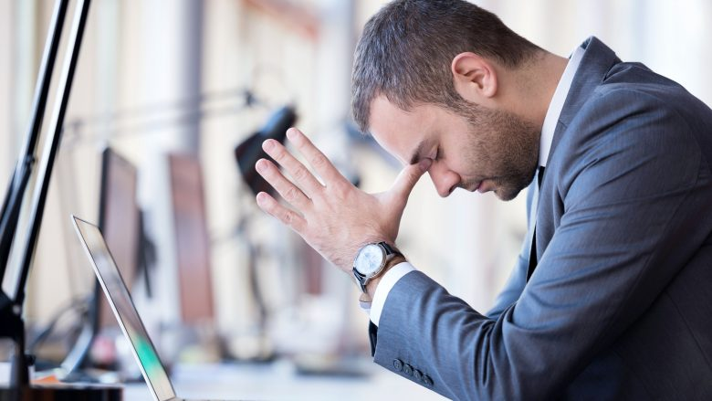 frustrated young business man working on laptop computer at office