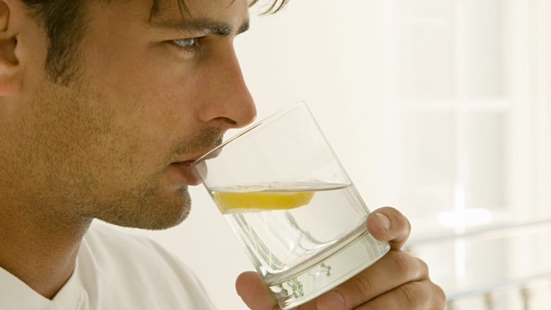 Man drinking water with lemon