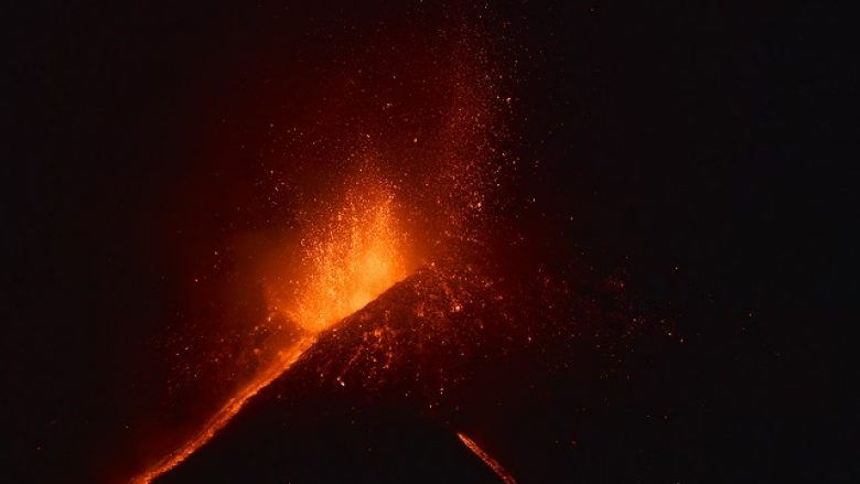 "Lava flows from the Mount Etna volcano on the southern Italian island of Sicily, near Catania, on December 6, 2015 at night. The volcano on the Mediterranean island threw up an ash column some seven kilometres (4.3 miles) high with lava flowing from the Voragine crater for the first time in two years, the National Institute of Geophysics and Vulcanology (INGV) said. The eruption, which began on December 3, 2015, is among the most ""energetic of the past 20 years,"" added the INGV.  AFP PHOTO / GIOVANNI ISOLINO / AFP PHOTO / GIOVANNI ISOLINO"