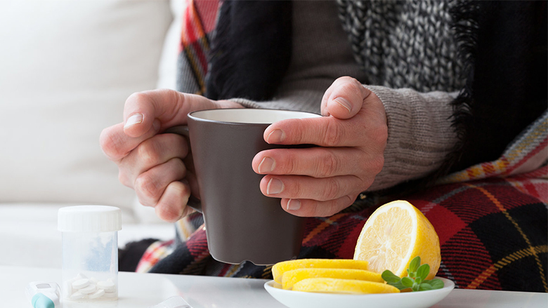 Ill man holding hot drink and warming up