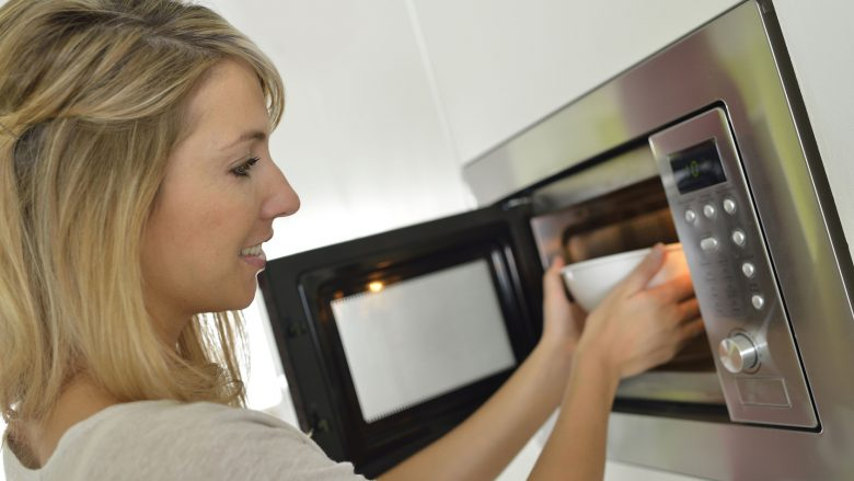 Woman at home using microwave oven
