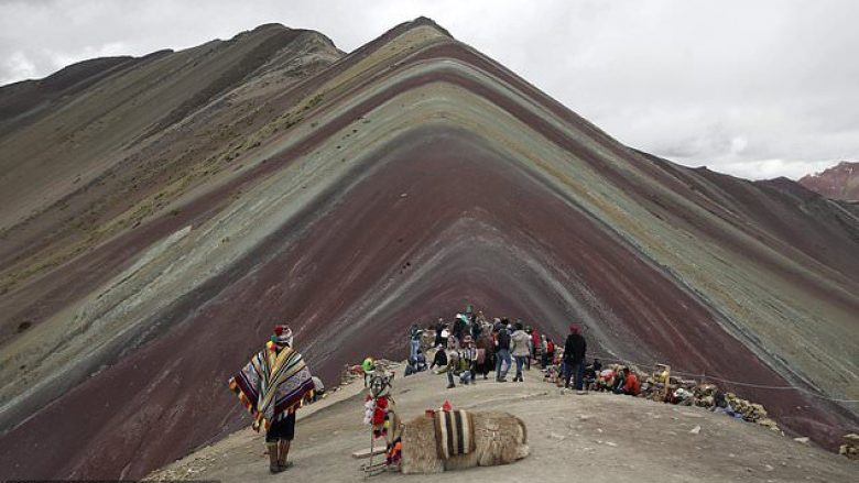 In this March 2, 2018 photo, an Andean man rests with his llama on Rainbow Mountain in Pitumarca, Peru. Tourists gasp for breath as they climb for two hours to the 16,404-foot (5,000-meter) peak in the Peruvian Andes, but stunned by the magical beauty that unfurls before them. (AP Photo/Martin Mejia)
