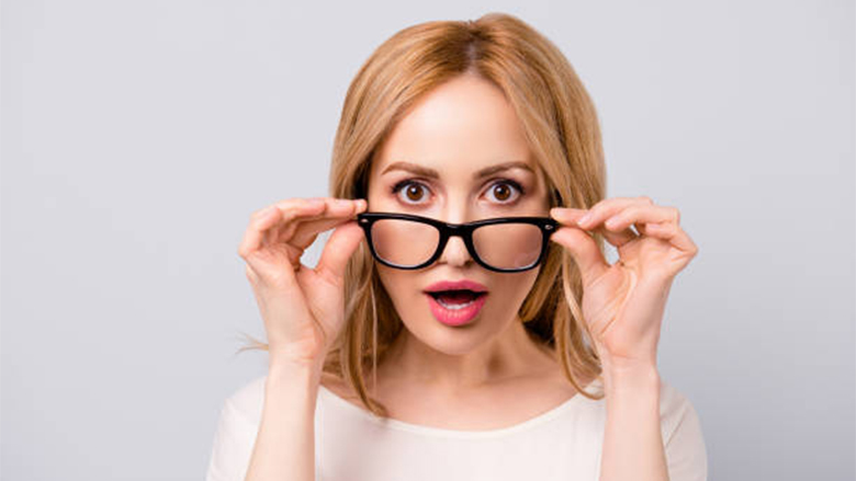 Attractive surprised business woman turning off her spectacles