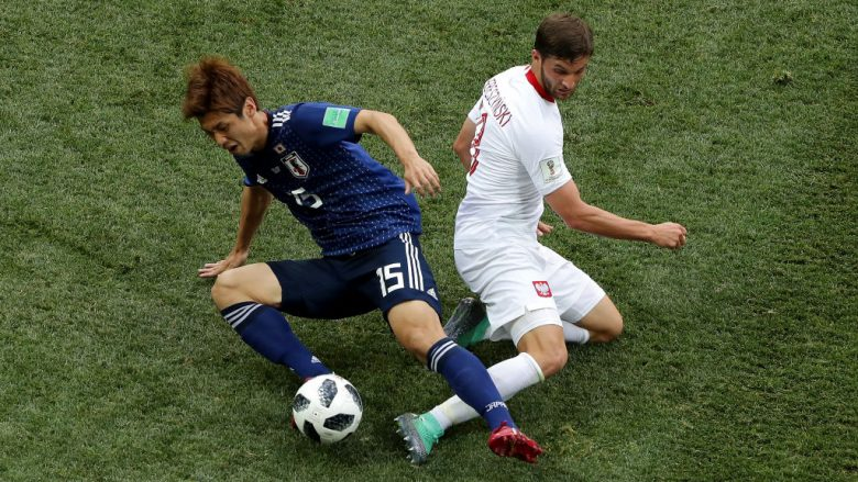 VOLGOGRAD, RUSSIA - JUNE 28:  Yuya Osako of Japan is tackled by Bartosz Bereszynski of Poland during the 2018 FIFA World Cup Russia group H match between Japan and Poland at Volgograd Arena on June 28, 2018 in Volgograd, Russia.  (Photo by Richard Heathcote/Getty Images)