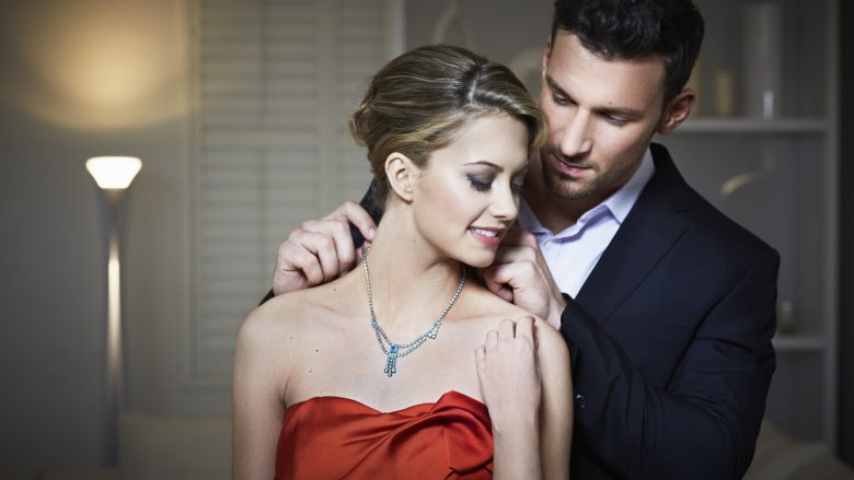 Man tying necklace on girlfriend