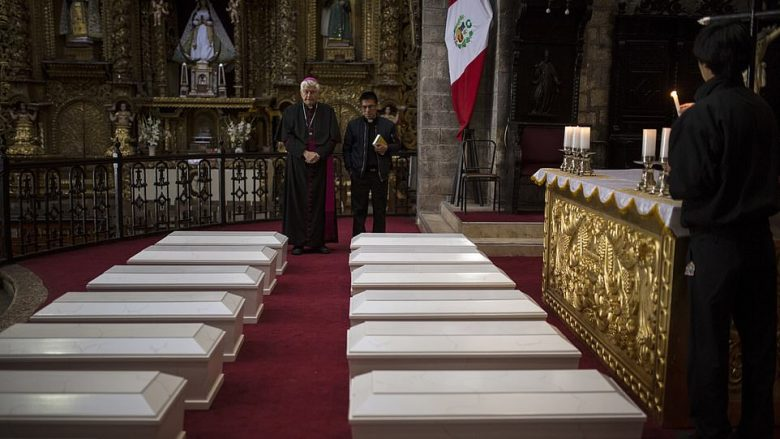 In this Aug. 14, 2018 photo, Ayacucho's Bishop Salvador Jose Miguel Pineiro, left, stands with an assistant behind the coffins of villagers who were killed by Shining Path guerrillas and the Peruvian army in the 1980s, inside the Cathedral in Ayacucho, Peru. More than 20,300 Peruvians are still considered disappeared in the struggle between Peru's military and Shining Path rebels during the 1980s and 1990s. (AP Photo/Rodrigo Abd)