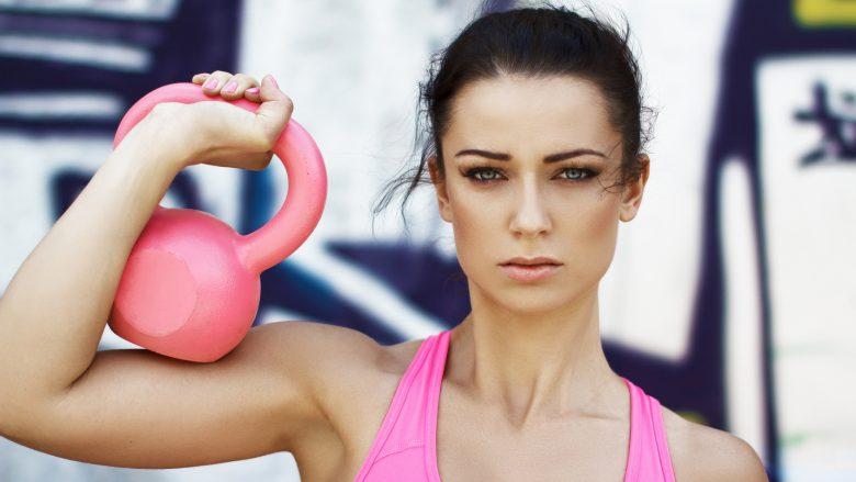 Woman holding pink kettlebell over shoulder, outdoor sport