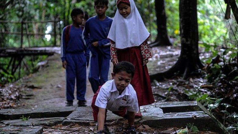 Nxënësi indonezian ndihmohet me duar për të ecur mbi tri kilometra që të shkojë në shkollë, shkaku i gjendjes së këmbëve (Video)