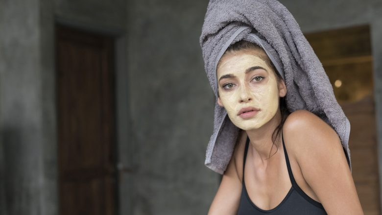 A young woman wearing a grey head towel is preparing for her facemask after a shower in a tropical balinese villa.