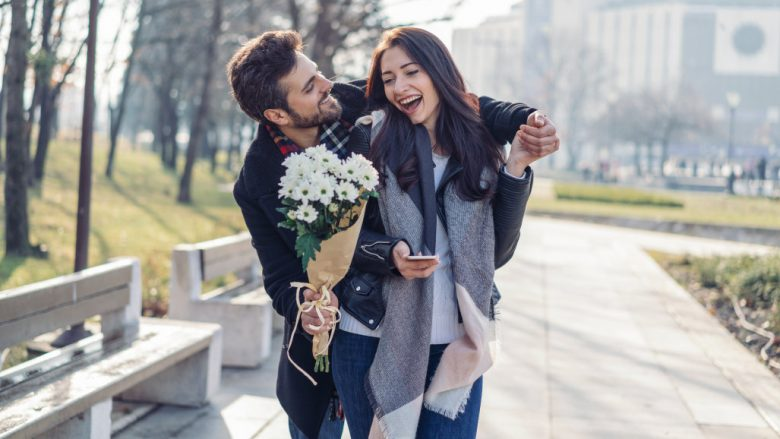 Beautiful woman being surprised by her boyfriend with white flowers bouquet