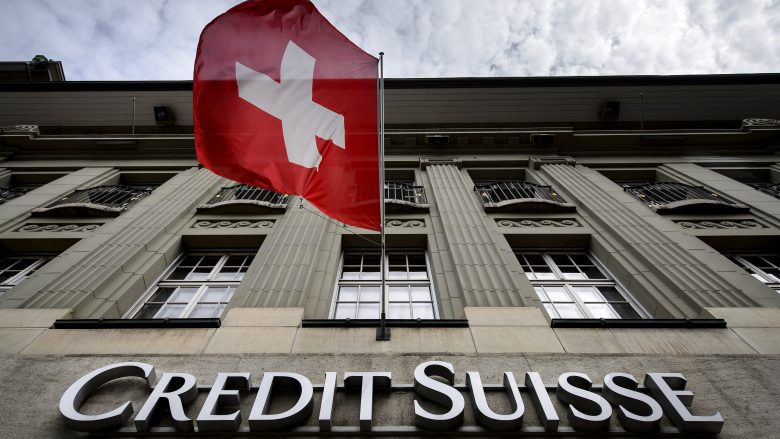 "A Swiss flag flies over a sign of Swiss bank Credit Suisse on May 8, 2014 in Bern. A senior US official told AFP on May 5, 2014 that the probe of Credit Suisse's past practice of helping its wealthy US clients evade taxes by sheltering their funds abroad was almost complete and that criminal charges could be brought within ""a few weeks."".   AFP PHOTO / FABRICE COFFRINI        (Photo credit should read FABRICE COFFRINI/AFP/Getty Images)"