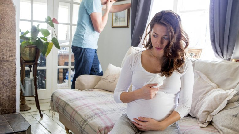 Pregnant couple having problems at home. Mum is crying on the sofa, dad is stood behing with his head in his hands.