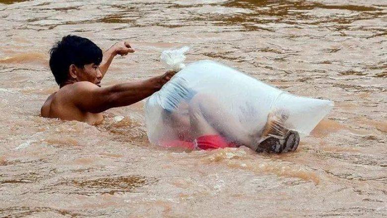 Për të shkuar në shkollë duhet të kalojnë lumin mbi të cilin nuk ka urë, prindërit detyrohen t'i fusin fëmijët në thasë të najlonit