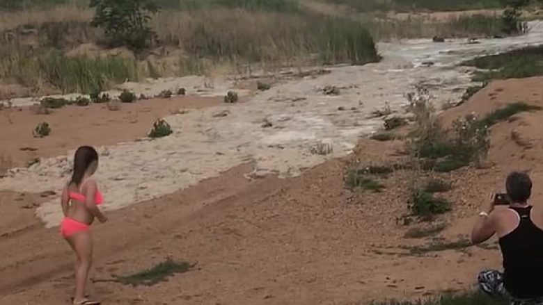 Familja shikojnë ujin që vinte përgjatë lumit të tharë – për herë të parë, pas disa vitesh