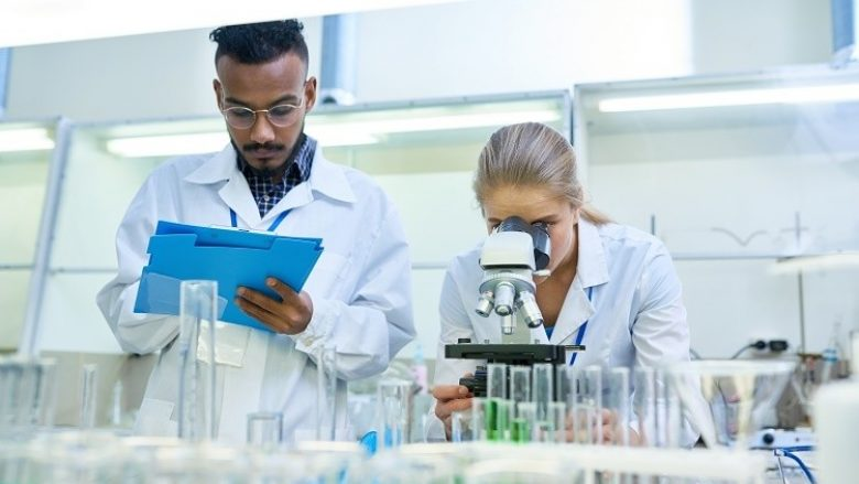 Portrait of young Middle-eastern scientist taking notes on clipboard while working on medical research in laboratory while his female colleague looking in microscope