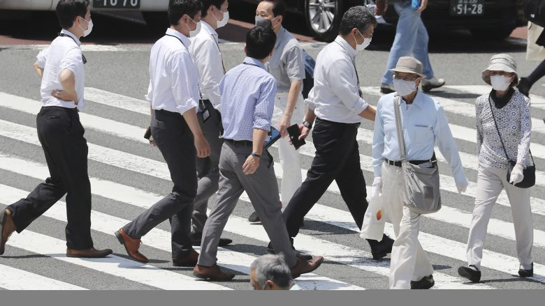 People wearing face masks to help protect against the spread of the new coronavirus walk on a street in Tokyo, Tuesday, Aug, 4, 2020. (AP Photo/Koji Sasahara)
