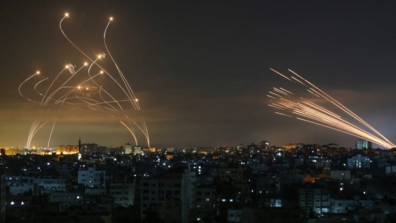 """TOPSHOT - The Israeli Iron Dome missile defence system (L) intercepts rockets (R) fired by the Hamas movement towards southern Israel from Beit Lahia in the northern Gaza Strip as seen in the sky above the Gaza Strip overnight on May 14, 2021. - Israel bombarded Gaza with artillery and air strikes on Friday, May 14, in response to a new barrage of rocket fire from the Hamas-run enclave, but stopped short of a ground offensive in the conflict that has now claimed more than 100 Palestinian lives. As the violence intensified, Israel said it was carrying out an attack """"in the Gaza Strip"""" although it later clarified there were no boots on the ground. (Photo by ANAS BABA / AFP)"""